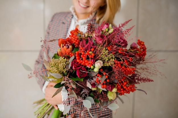Mulher segurando um buquê brilhante de flores nas mãos