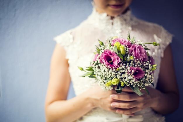 Mulher segurando um buquê colorido com as mãos no dia do casamento
