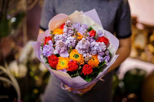 Mulher segurando um buquê composto por tulipas vermelhas, ranúnculo lilás e laranja