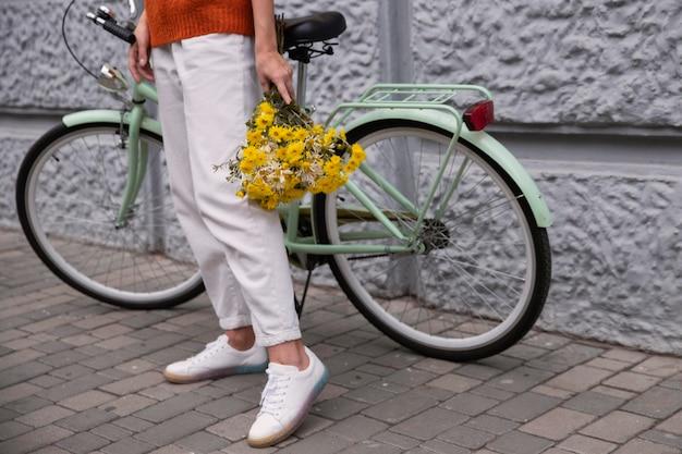 Mulher segurando um buquê de flores com sua bicicleta do lado de fora
