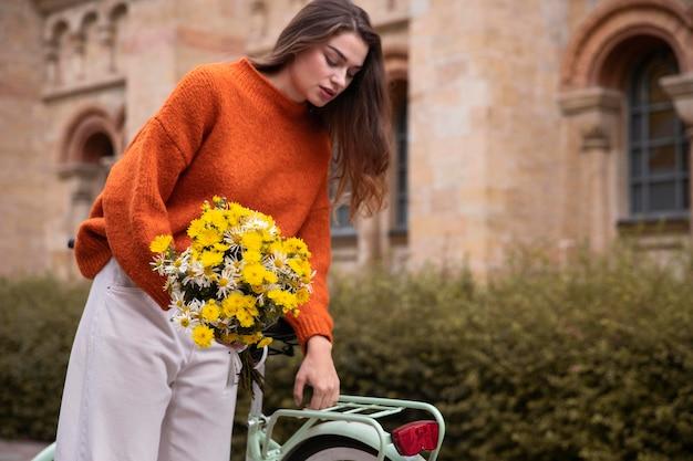 Mulher segurando um buquê de flores enquanto está sentada ao lado de uma bicicleta