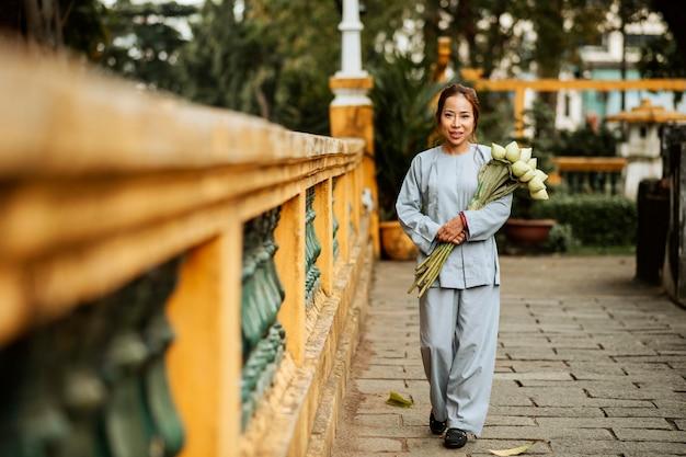Mulher segurando um buquê de flores no templo