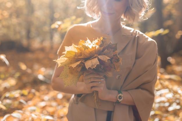 Mulher segurando um buquê de folhas de bordo de outono, temporada e conceito de outono