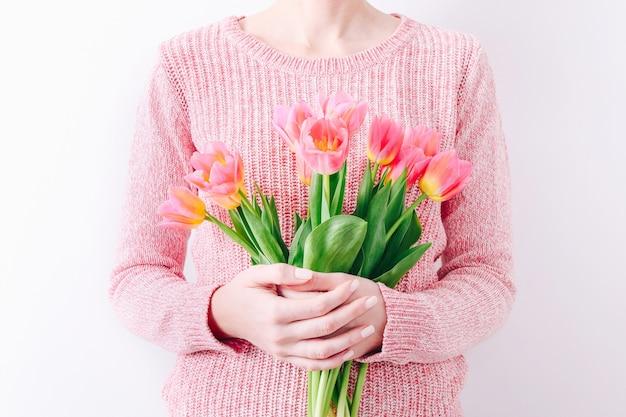 Mulher segurando um buquê de primavera de tulipas cor de rosa nas mãos.