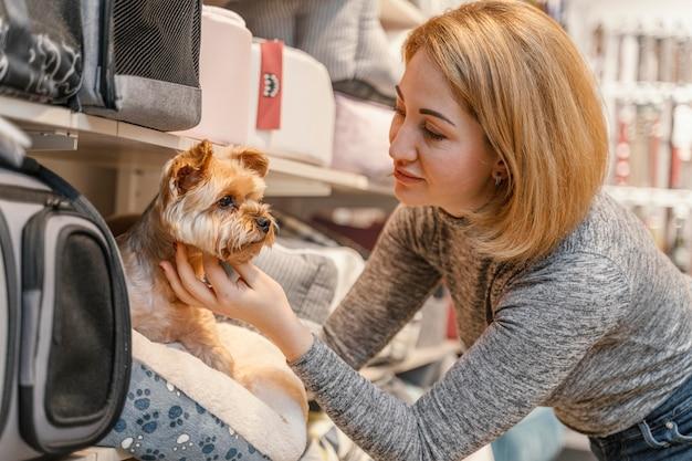 Mulher segurando um cachorrinho fofo na loja de animais