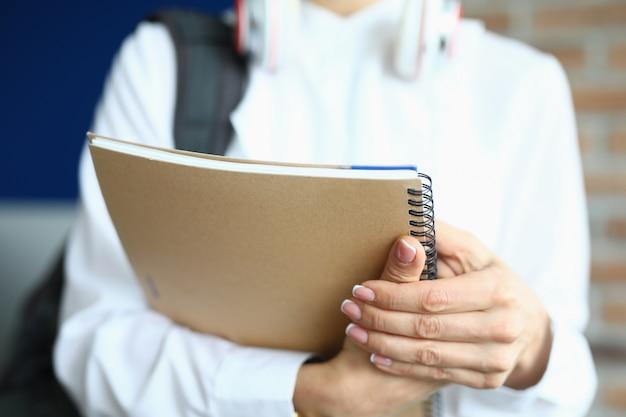 Mulher segurando um caderno em uma mola para os exames