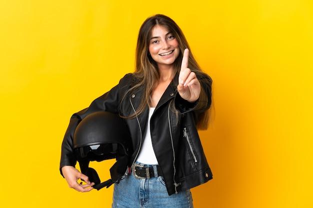 Mulher segurando um capacete de motociclista isolado na parede amarela, mostrando e levantando um dedo