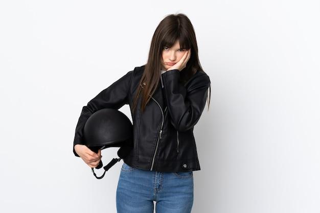 Mulher segurando um capacete de motociclista isolado na parede branca, infeliz e frustrada