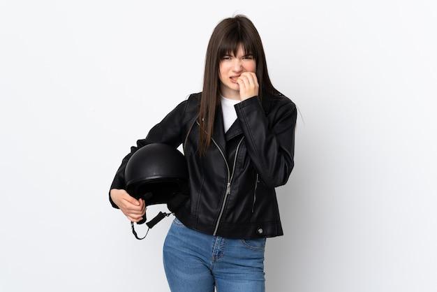 Mulher segurando um capacete de motociclista isolado na parede branca, nervosa e assustada