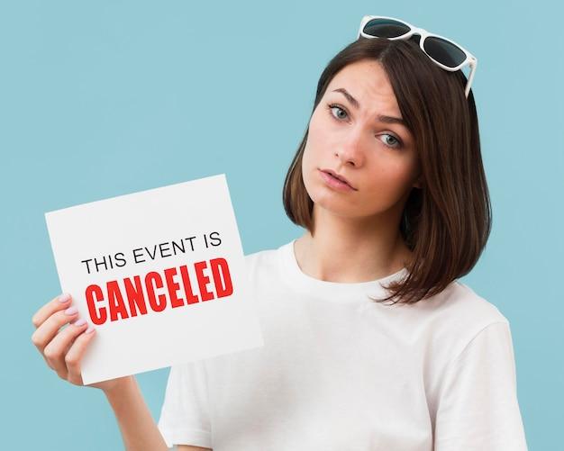 Mulher segurando um cartão com uma mensagem de evento cancelado