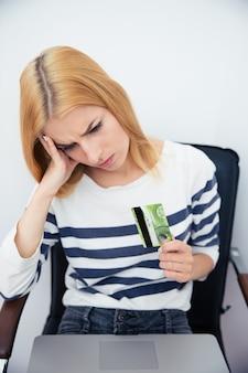 Mulher segurando um cartão de banco