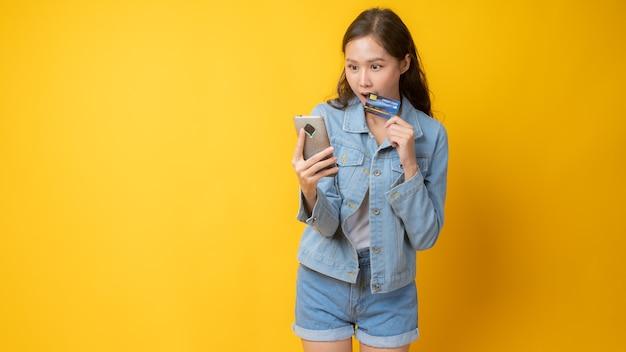 Mulher segurando um cartão de crédito com o telefone em fundo amarelo
