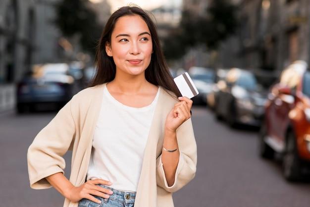 Mulher segurando um cartão de crédito e pensando em fazer compras