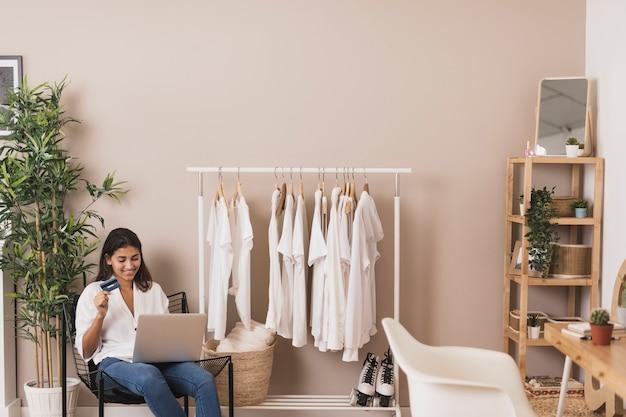 Mulher segurando um cartão de crédito e trabalhando no laptop