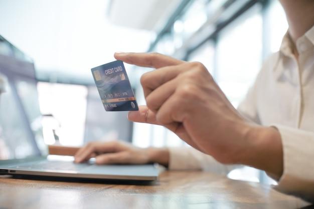 Mulher segurando um cartão de crédito e usando um laptop