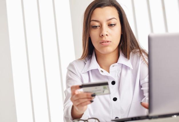 Mulher segurando um cartão de crédito no laptop para o conceito de compras online
