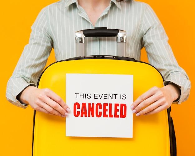 Mulher segurando um cartão de evento cancelado