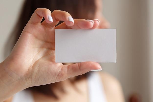 Mulher segurando um cartão de visita na mão fechar