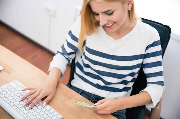 Mulher segurando um cartão do banco e digitando no teclado