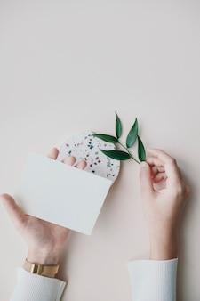 Mulher segurando um cartão em branco com folhas de ruscus