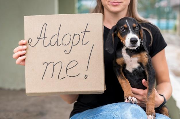 Mulher segurando um cartaz de adote-me e resgate o cachorro