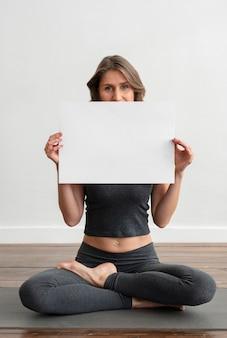 Mulher segurando um cartaz em branco enquanto pratica ioga