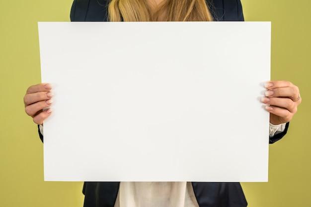 Mulher segurando um cartaz em branco sobre fundo verde