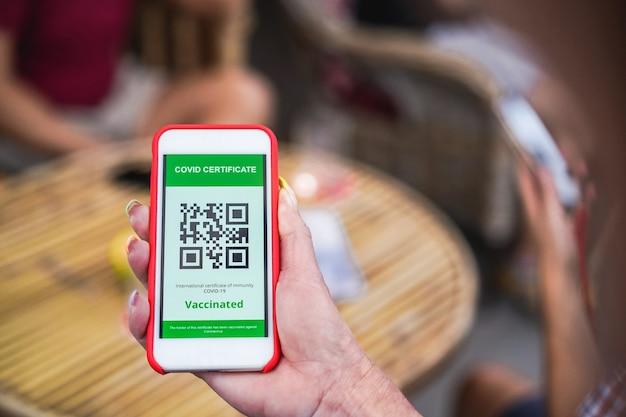 Mulher segurando um celular com um cobiçado certificado de código qr em frente ao bar restaurante
