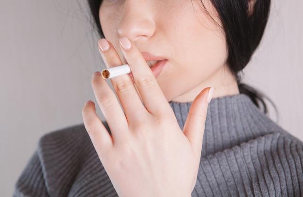Mulher segurando um cigarro na mão