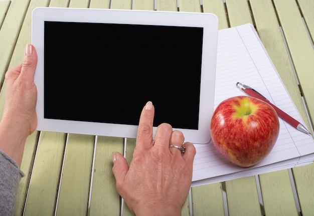 Mulher segurando um computador tablet com uma maçã