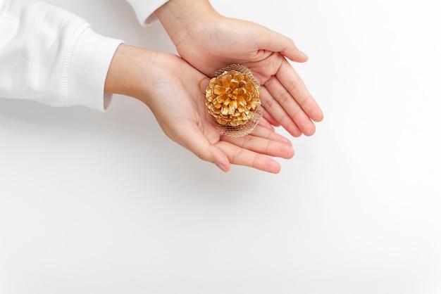 Mulher segurando um cone dourado de conífera na palma da mão