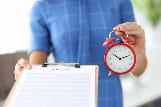 Mulher segurando um contrato e um despertador vermelho nas mãos.