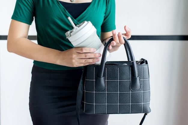 Mulher segurando um copo de água reutilizável