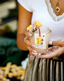 Mulher segurando um copo de bebida com gelo decorado com forro de isgum amor
