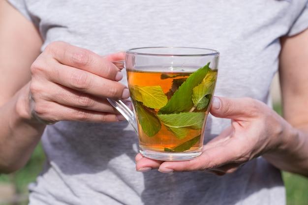 Mulher segurando um copo de chá de menta nas mãos