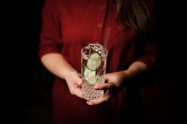 Mulher segurando um copo de cocktail com bebida alcoólica fresca com fatias de pepino e gin