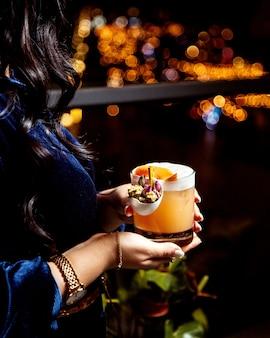 Mulher segurando um copo de cocktail laranja, olhando a vista da cidade à noite