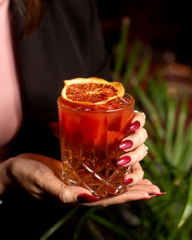 Mulher segurando um copo de cocktail vermelho decorado com fatia de laranja seca