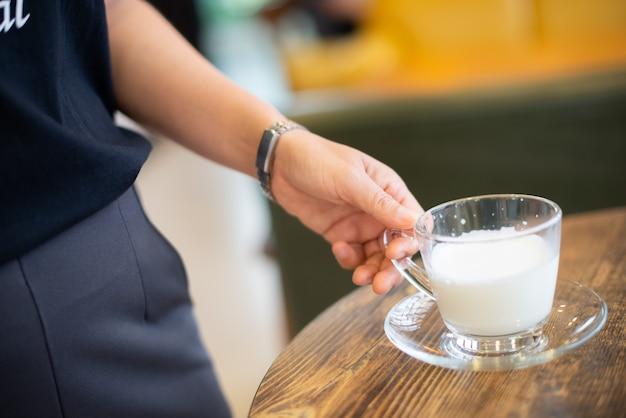 Mulher segurando um copo de leite quente em cima da mesa