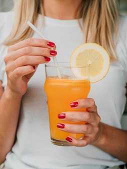 Mulher segurando um copo de suco de laranja e palha