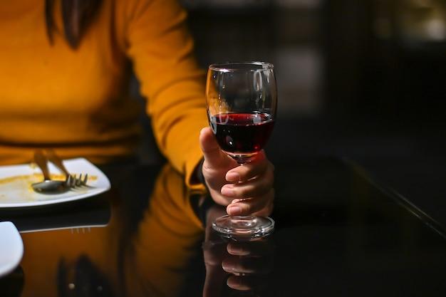 Mulher segurando um copo de vinho tinto com tom vintage.