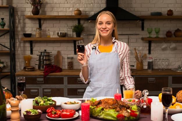 Mulher segurando um copo de vinho tinto e sorriso