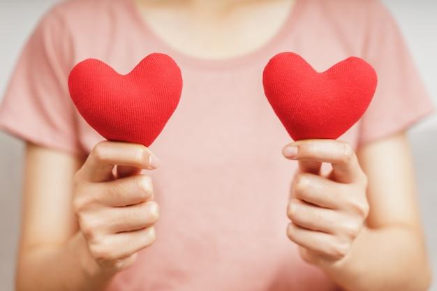 Mulher segurando um coração vermelho, amor, seguro de saúde, doação, voluntária de caridade feliz, dia mundial da saúde mental, dia mundial do coração, dia dos namorados