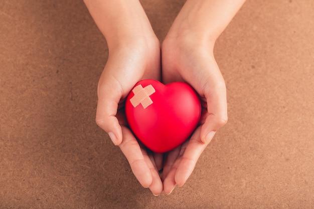 Mulher segurando um coração vermelho com bandagem em fundo de madeira. conceito de cuidados de saúde.
