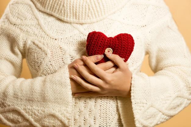 Mulher segurando um coração vermelho no peito