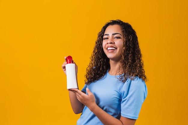 Mulher segurando um creme em fundo amarelo