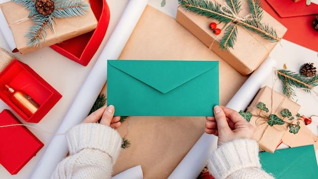 Mulher segurando um envelope enquanto embrulha presentes para um natal em uma mesa