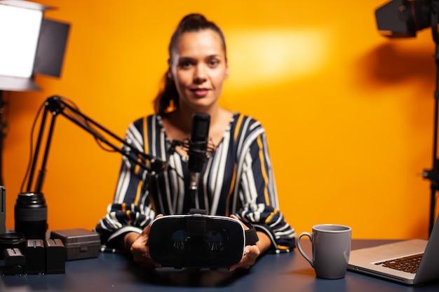 Mulher segurando um fone de ouvido enquanto grava o videoblog no estúdio caseiro