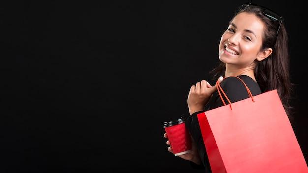 Mulher segurando um grande espaço de cópia de sacola de compras vermelha