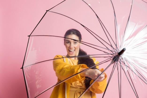 Mulher segurando um guarda-chuva aberto na frente dela